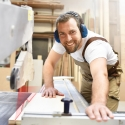 Tischler sgt Holzbrett in einer Schreinerei // Carpenter sawing wooden board in a carpenter's workshop